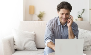Cheerful Entrepreneur Talking On Phone Using Laptop At Home